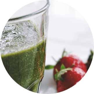 A glass with green superfoods and strawberries form part of a healthy breakfast
