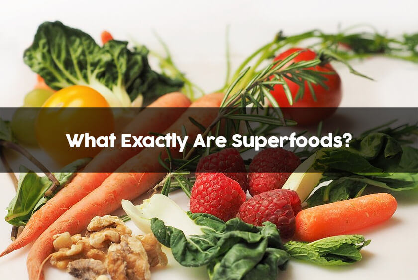 A kitchen table with many superfoods including spinach, carrots, walnuts, berries, and others.