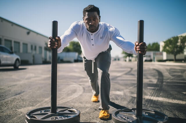 A man pushes heavy weights on the ground as an exercise for his core and legs for his fitness and wellness goals.