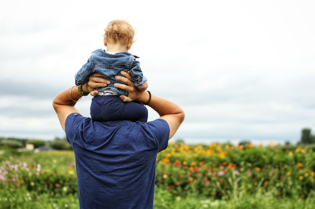 Father carries son on his shoulders in a sunny spring day after drinking his daily superfoods
