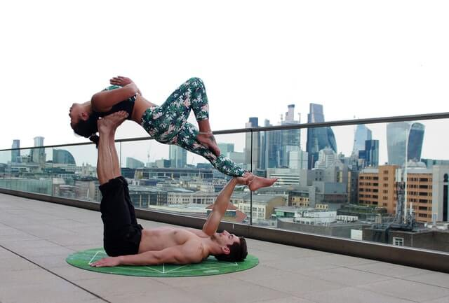 A couple doing acroyoga also shares healthy habits at home, including drinking their PhytoFood superfoods everyday.