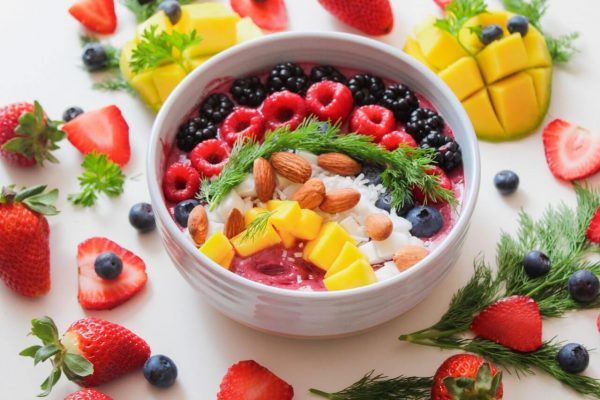 A superfoods bowl with raspberries, blackberries, mango, almond, acai, coconut, and more.