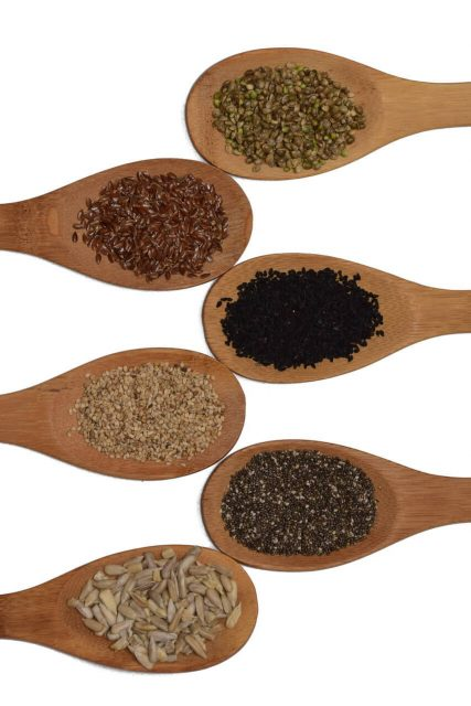 Kitchen spoons demonstrating different types of fiber and seeds such as chia seeds, flax seeds, quinoa, and others.
